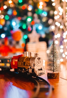 Zabawkarska rocznik lokomotywa parowa na podłodze pod dekorowaną choinką na bokeh zaświeca girlandę.