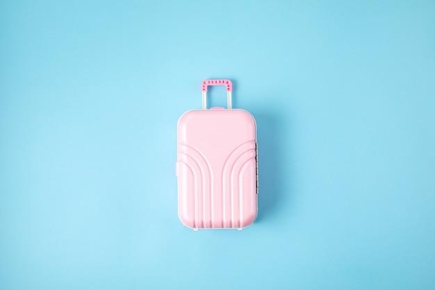 Zabawkarska różowa walizka na błękitnym tle
