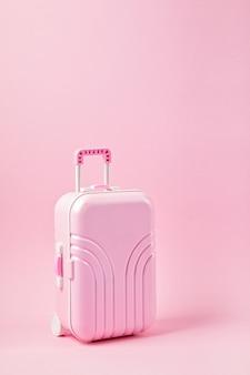 Zabawkarska różowa walizka na różowym tle