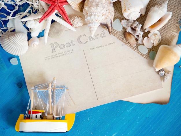 Zabawkarska żaglówka, sieć i seashells na błękitnym drewnianym ściennym odgórnym widoku z pocztówkową papierowej kopii przestrzenią