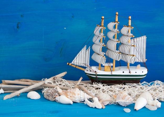 Zabawkarska żaglówka, wietrzejący drewna, sieć i seashells na błękitnym drewnianej ściany zakończeniu up z kopii przestrzenią