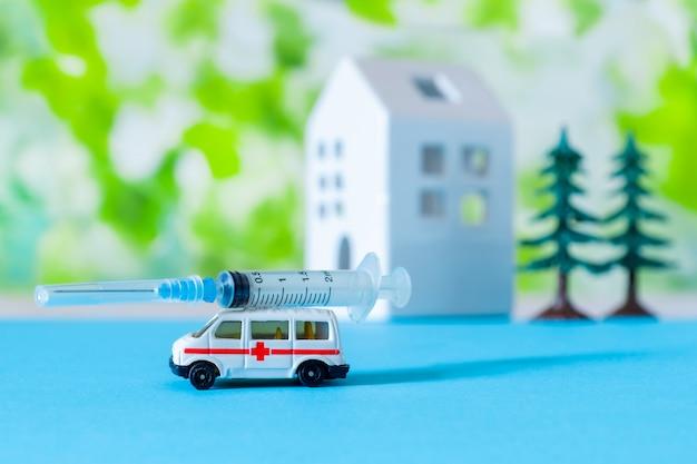 Zabawkarski ambulansowy samochodowy strzykawki błękita zieleni szpitala znaka tła domu covid 19 drzewo