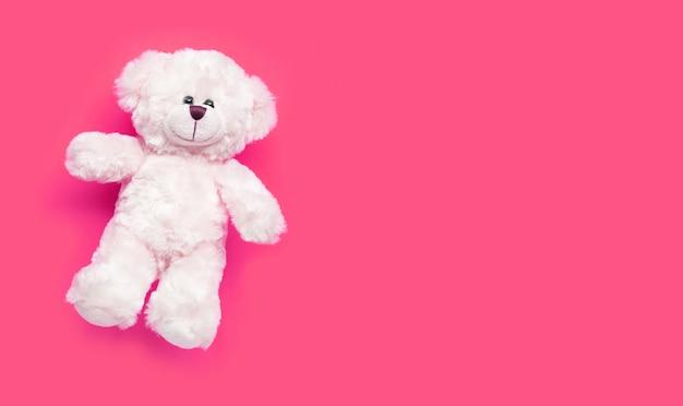 Zabawkarski biały niedźwiedź na różowym tle.