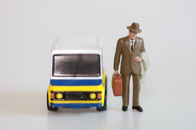 Zabawkarski biznesmen blisko samochodu dostawczego na białym tle