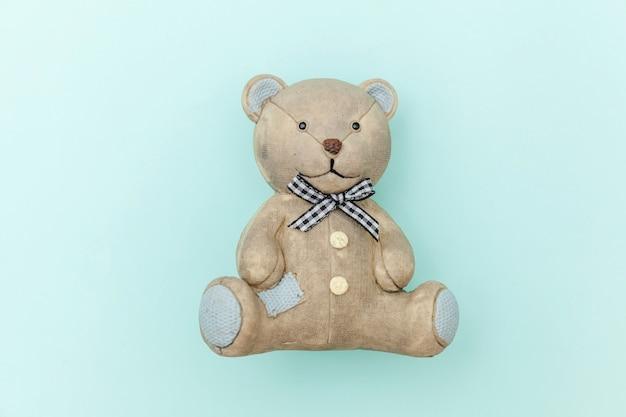 Zabawkarski niedźwiedź odizolowywający na pastelowym błękicie