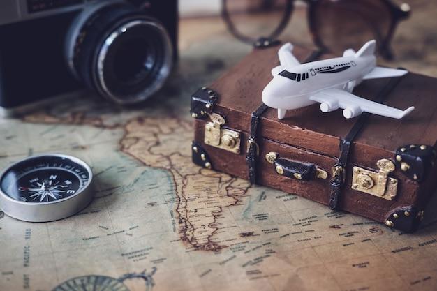 Zabawkarski samolot i walizka na rocznik mapie z kopii przestrzenią