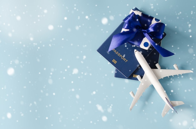 Zabawkarski samolot z paszportami i prezenta pudełkiem na błękitnym tle.