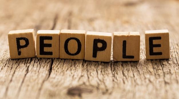Zabawki cegły na stole z ludźmi słowa