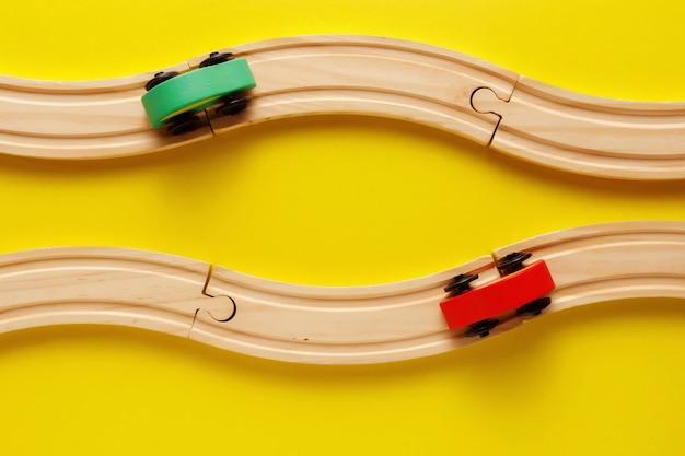 Zabawki dla dzieci ramki na żółtym backround, zabawki drewniane kolejowe i pociąg. widok z góry. flatlay. skopiuj miejsce na tekst