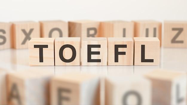 Zabawki drewniane klocki z literami toef na stole. toefl - skrót do testu znajomości języka angielskiego jako obcego