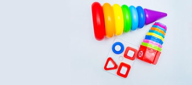 Zabawki edukacyjne dla dzieci piramida i sortery leżą na białym tle z miejscem na tekst top...