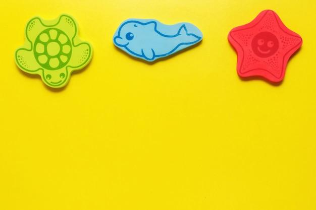 Zabawki flatlay na żółtym tle. życie morskie. makieta projektu z miejsca kopiowania.