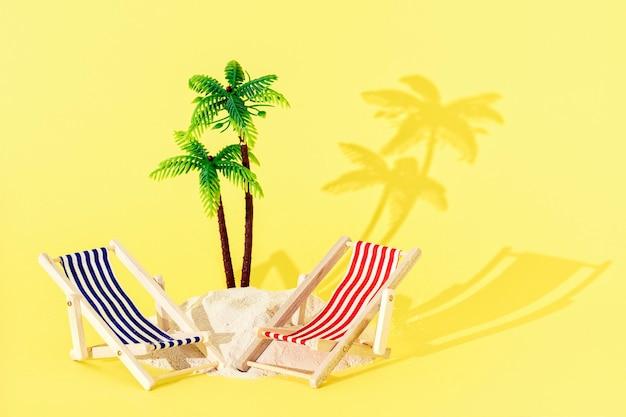 Zabawki mini leżaki plażowe i palma z piaskiem i cieniem na żółtym tle. koncepcja kreatywnych lato plaża.