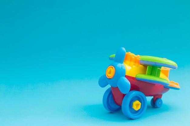 Zabawki modelują samolot, samolotowy kolorowy model na błękitnym tle.