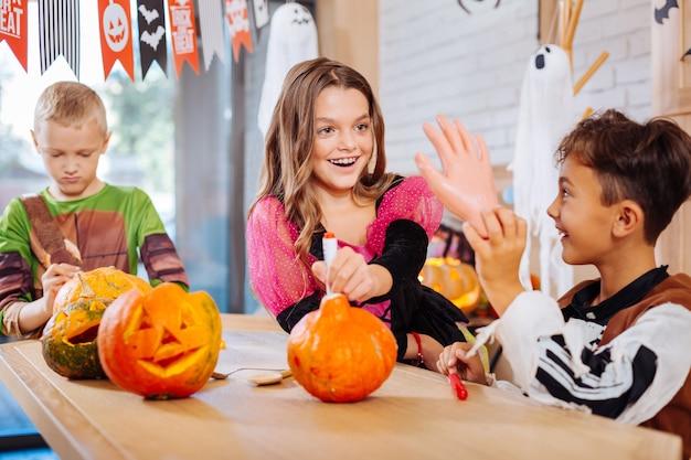 Zabawki na halloween. troje dzieci ubranych w ładne kostiumy czuje się śmiesznie, trzymając przerażające zabawki na halloween na imprezę