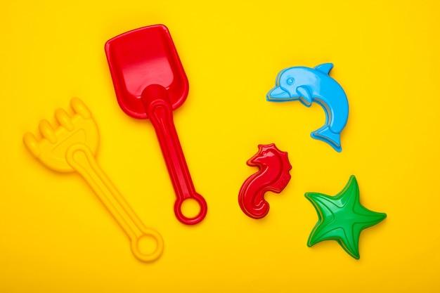 Zabawki plażowe dla dzieci lub zabawki piaskownicy na żółtym tle