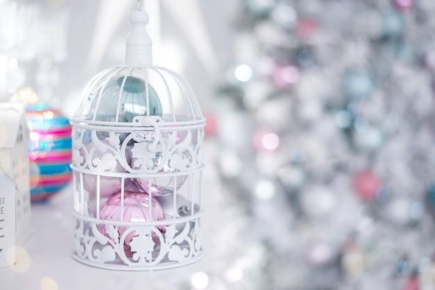 Zabawki świąteczne bombki srebrno-niebieski różowy w białej ażurowej klatce na tle lampek choinkowych.