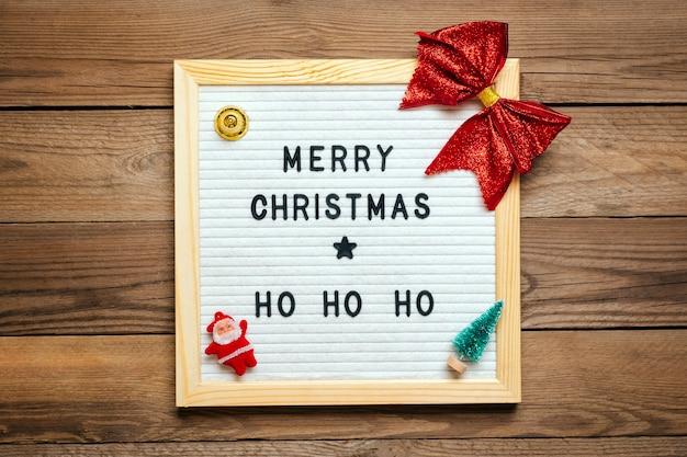 Zabawki świąteczne - łuk, święty mikołaj, dzwonek, choinka na podłoże drewniane.