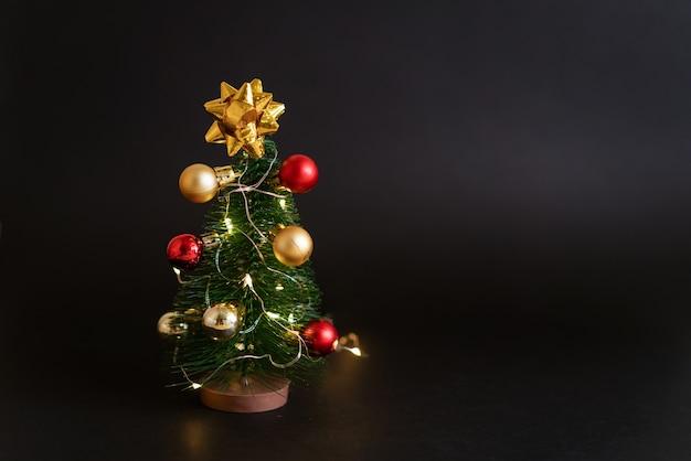 Zabawkowa choinka z kulkami na czarnym tle z girlandą uroczy świąteczny wystrój w ciemnym stylu