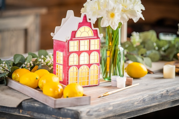Zabawkowa dekoracyjna lampka stoi na drewnianym stole wśród wiosennych kwiatów i elementów wyposażenia wnętrz.