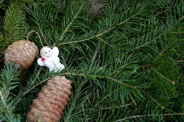 Zabawkowa figurka anioła na tle gałęzi zjadana ze stożkiem