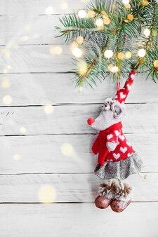 Zabawkowa mysz w czapce i spódnicy na świerkowej gałęzi na białym drewnianym tle ze złotymi światłami
