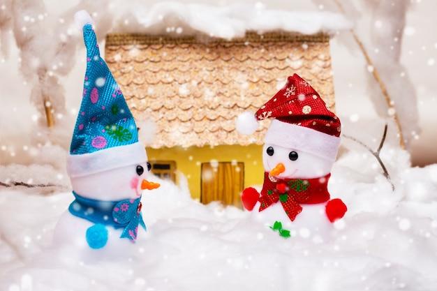 Zabawkowe bałwanki w śniegu w pobliżu domu podczas opadów śniegu_