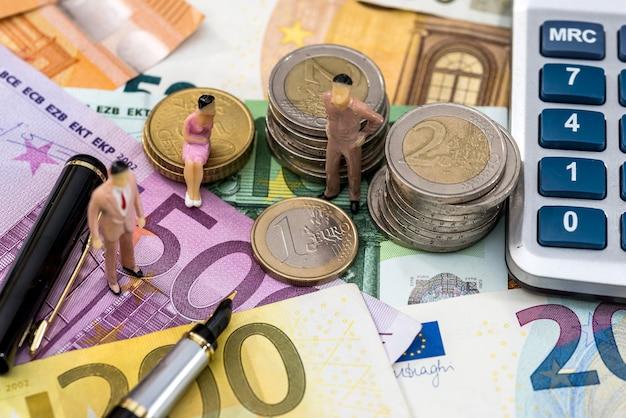 Zabawkowe osoby siedzą na monetach euro z kalkulatorem, długopisem i rachunkami euro