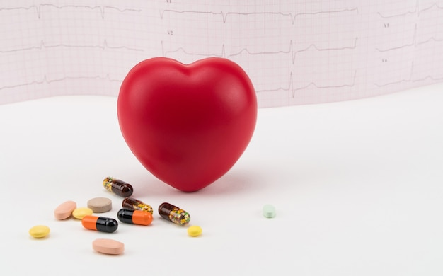 Zabawkowe serce z pigułkami na tle elektrokardiogramu kardiologia opieki serca