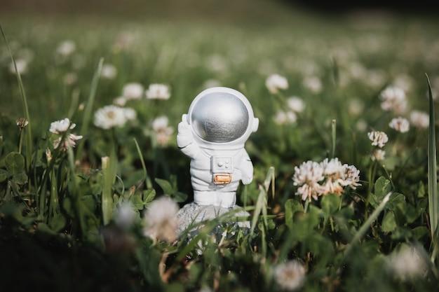 Zabawkowy astronauta stoi w wysokiej trawie i macha ręką