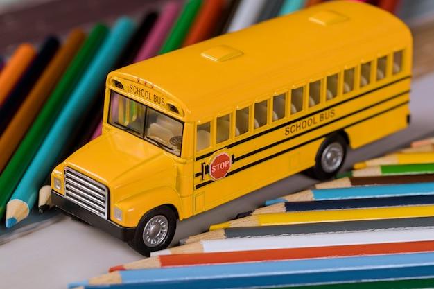 Zabawkowy autobus szkolny z kolorowymi drewnianymi ołówkami.