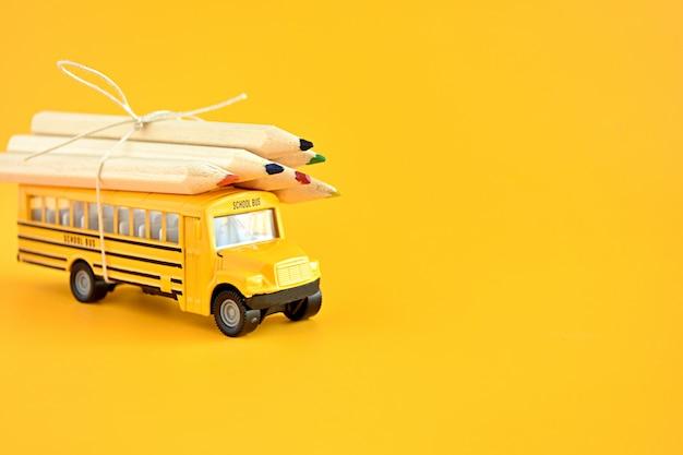Zabawkowy autobus szkolny z ołówkami na dachu.
