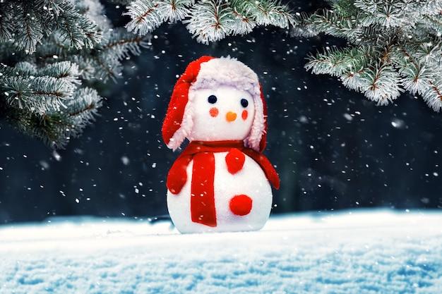 Zabawkowy bałwan na śniegu w pobliżu śnieżnego świerka podczas opadów śniegu, kartki z życzeniami noworocznymi i bożonarodzeniowymi