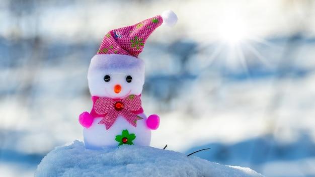 Zabawkowy bałwan w lesie na śniegu przy słonecznej pogodzie