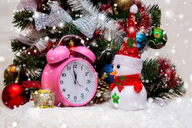 Zabawkowy bałwan w pobliżu zegara, który pokazuje zbliżanie się 12 godzin, nowego roku. bałwan, zegar przy choince, pada śnieg