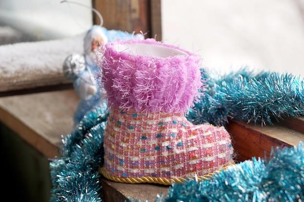 Zabawkowy bożonarodzeniowy but w zimowym oknie