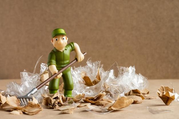 Zabawkowy człowiek w pracowniczym garniturze grabi dużą ilość śmieci. pojęcie ochrony środowiska i ekologii.