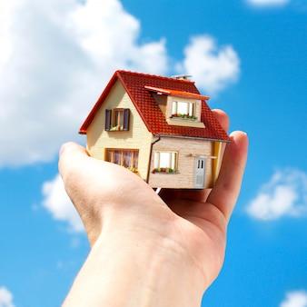 Zabawkowy dom w ludzkiej dłoni na niebie