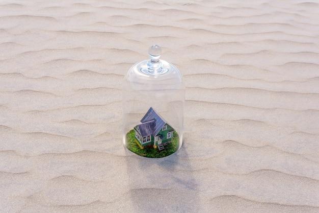Zabawkowy dom z tektury z zielonym trawnikiem chronionym szklaną kopułą wśród martwej piaszczystej pustyni