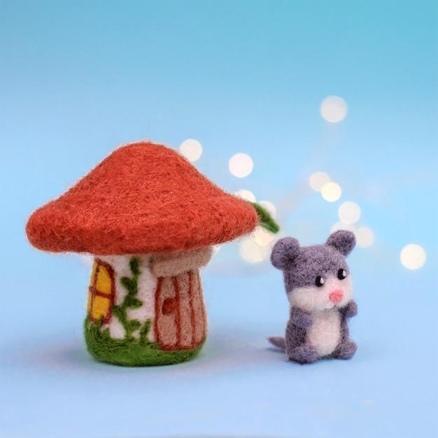 Zabawkowy grzyb domowy z drzwiami i oknami oraz śliczną małą szarą myszką na jasnoniebieskim tle z bokeh