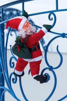 Zabawkowy mikołaj wspina się z torbą prezentów na balkonie chaty wzdłuż balustrady