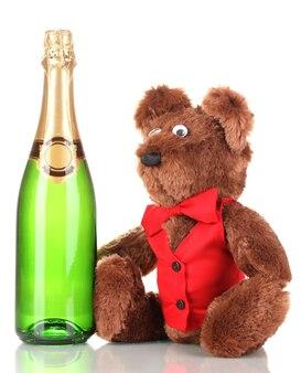 Zabawkowy miś i butelka szampana na białym tle