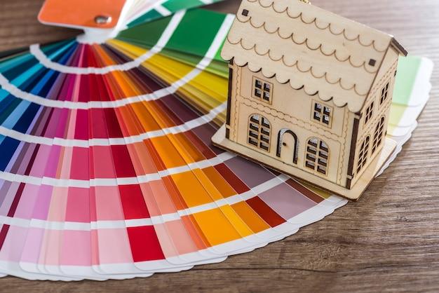 Zabawkowy model drewnianego domu na próbce koloru