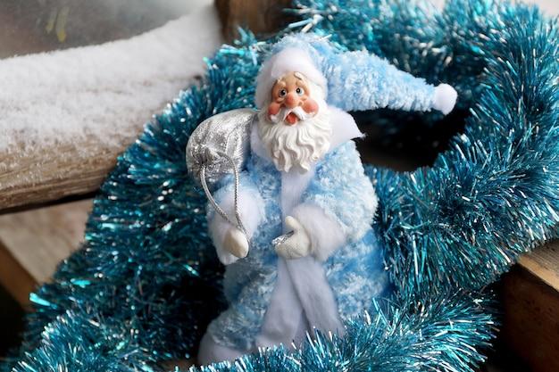 Zabawkowy ojciec mróz w niebieskim futrze ze srebrzystą torbą