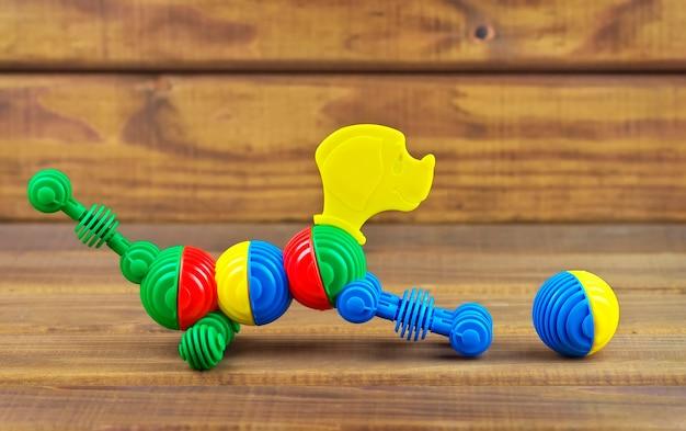 Zabawkowy piesek wykonany z plastikowych kolorowych detali i piłki na drewnianym tle. pies bawić się piłką.
