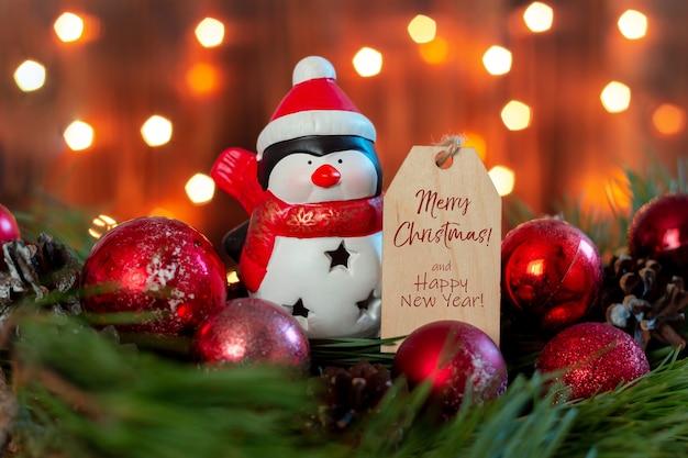 Zabawkowy pingwin mikołaja z drewnianą notatką z tekstem powitania wesołych świąt i szczęśliwego nowego roku