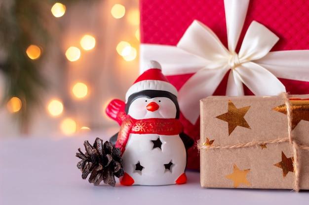 Zabawkowy pingwin w czapce mikołaja i rożku obok pudełek z prezentami ozdób choinkowych i sylwestrowych