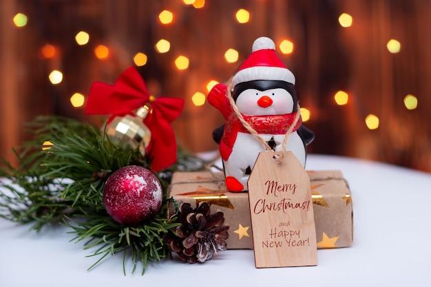 Zabawkowy pingwin z notatką z tekstem wesołych świąt i szczęśliwego nowego roku na tle bokeh