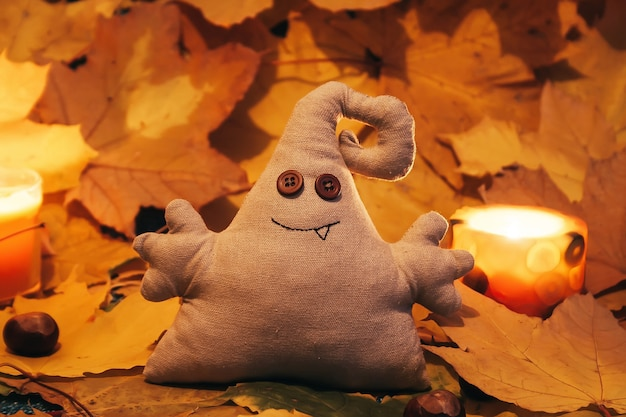 Zabawkowy potwór z guzikowymi oczami wśród liści i świec