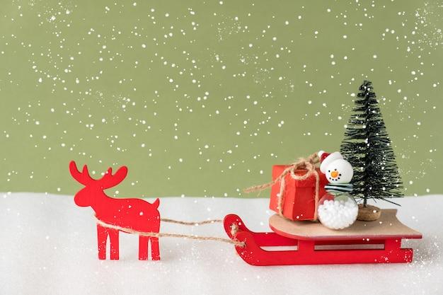 Zabawkowy renifer i sanie dostarczające świąteczny prezent i choinkę